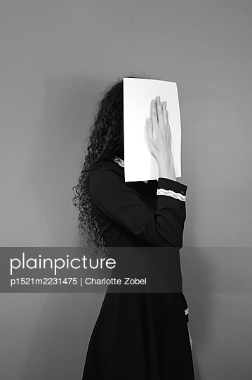 Young woman with sheet of paper in front of her face - p1521m2231475 by Charlotte Zobel