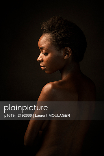 Portrait of a young black woman facing down with her eyes closed - p1619m2192686 by Laurent MOULAGER