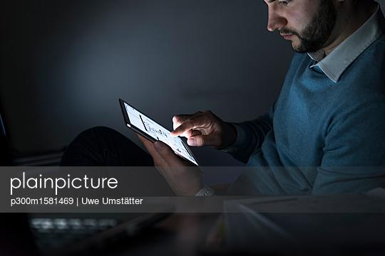 Businessman working on tablet in office at night - p300m1581469 von Uwe Umstätter