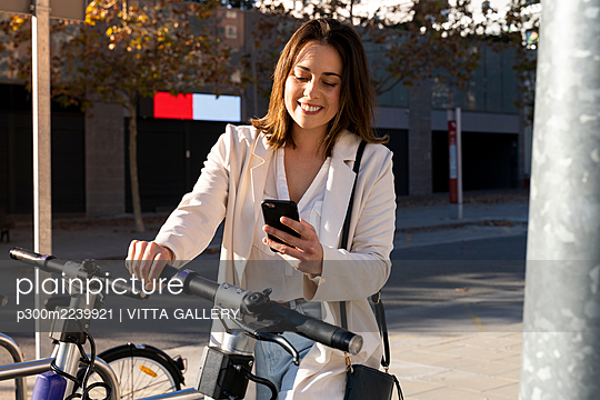 Smiling businesswoman doing contactless payment while standing at bicycle parking station - p300m2239921 by VITTA GALLERY