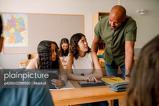 Male teacher teaching teenage girls over digital tablet at desk in classroom - p426m2298550 by Maskot