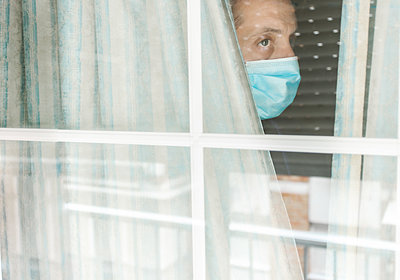 Photo of a Middle-aged white man with medical face mask looking out of the window during coronavirus quarantine - p1166m2189816 by Cavan Images