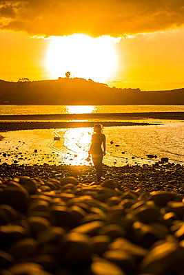 Woman on the waterfront at sunset, New Zealand - p1455m2204861 by Ingmar Wein