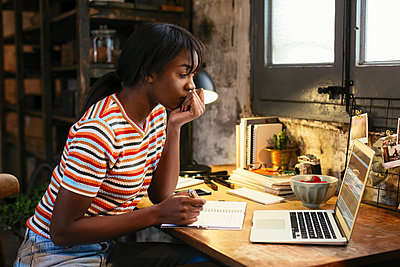Pensive young woman sitting at desk in a loft looking at laptop - p300m1581335 by Bonninstudio