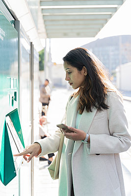 Young woman using ticket machine at tram stop - p300m2166209 by VITTA GALLERY