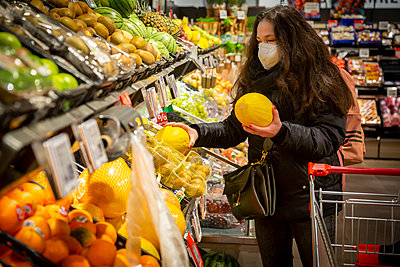 Mature woman buying fruits in supermarket during COVID-19 - p300m2243316 by Nadine Ginzel