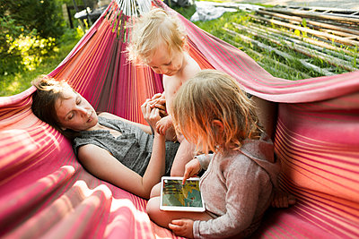 Sweden, Skane, Mother, daughter (4-5) and son (2-3) resting in hammock - p352m1349736 by Viktor Holm