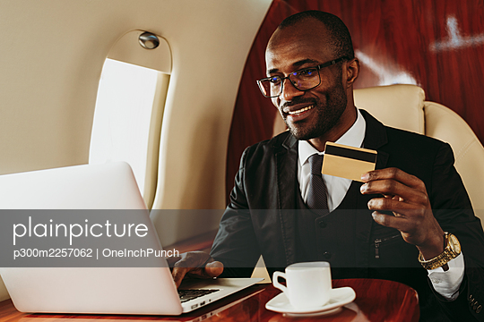 Smiling businessman with credit doing online shopping through laptop in airplane - p300m2257062 by OneInchPunch