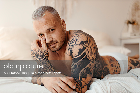 Serious man with tattoo lying on bed at home - p300m2276198 by Gala Martínez López