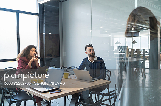 Male and female professionals looking at businesswoman in office - p300m2282795 by SERGIO NIEVAS