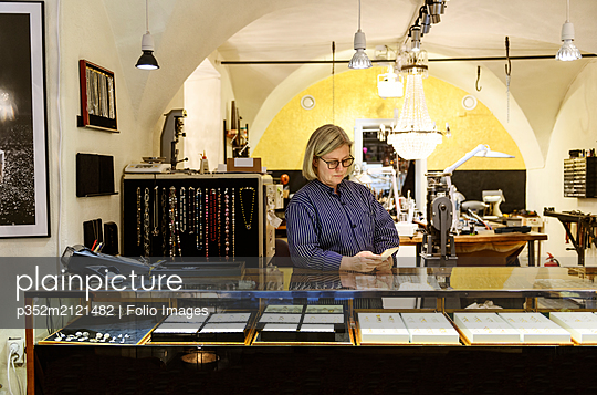 Goldsmith using smart phone at counter of her jewellery store - p352m2121482 by Folio Images