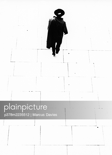 Man in long coat and hat - p378m2235512 by Marcus Davies