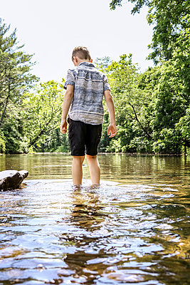 Boy wading through shallow water in the river - p1019m1462177 by Stephen Carroll