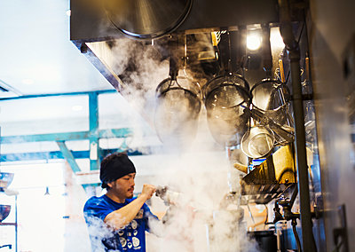 The ramen noodle shop. A chef working in a kitchen with steam rising from the pots of noodles. - p1100m1185679 by Mint Images