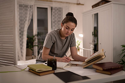 Young student preparing for exams at home - p1166m2236269 by Cavan Images