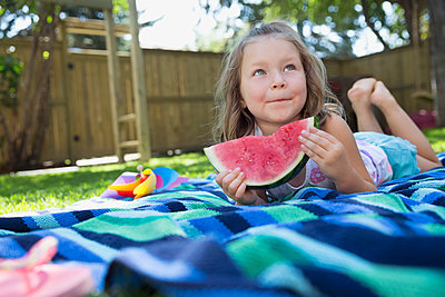 Girl laying on blanket eating watermelon in backyard - p1192m1183954 by Hero Images