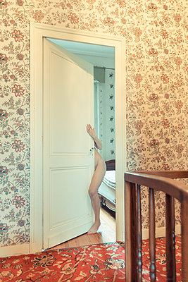 Female body hidden behind a door open in an old french house - p1619m2192706 by Laurent MOULAGER