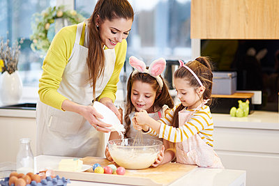Mother and daughters baking Easter cookies in kitchen together - p300m1567649 by gpointstudio