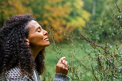 Curly hair woman with eyes closed smelling plant in forest - p300m2250259 by Annika List