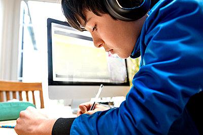 UK, Boy (10-11) in headphones having on-line lesson - p924m2271291 by Bonfanti Diego