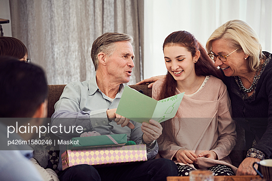 Grandfather reading greeting card to happy family while sitting on sofa at home - p426m1580246 by Maskot