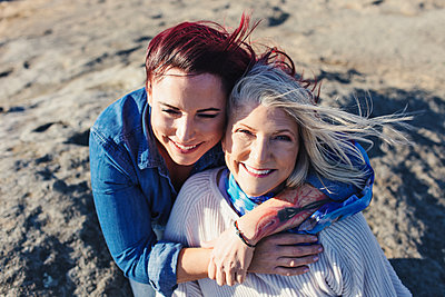 High angle portrait of cheerful mother with daughter on rocks - p1166m1509667 by Cavan Images