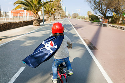 Spain, Barcelona, back view of little boy with a pirate cape riding bicycle on an empty street - p300m1130197f von Valentina Barreto