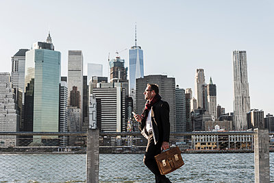 USA, Brooklyn, businessman with briefcase standing in front of Manhattan skyline - p300m1205180 by Uwe Umstätter