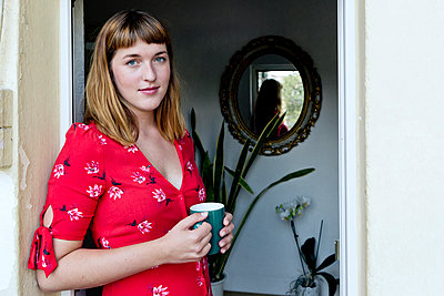 Portrait of young woman with cup of coffee standing on balcony - p300m2131853 by FL photography