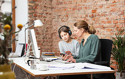 Girl with wireless headphones using mobile phone by mother at desk in home office - p300m2273970 by Studio 27