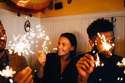 Smiling young woman with multi-ethnic male friends holding sparklers in restaurant during dinner party - p426m2046299 by Maskot
