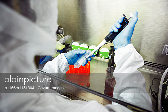 Scientist using pipette during experiment in laboratory - p1166m1151304 by Cavan Images