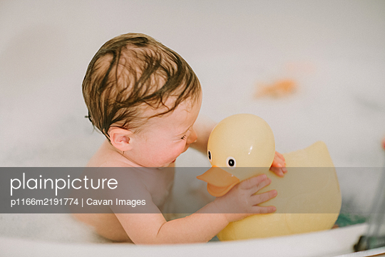 Baby in bath playing with big rubber duck - p1166m2191774 by Cavan Images