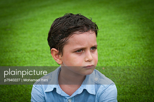 Upset little boy looking away