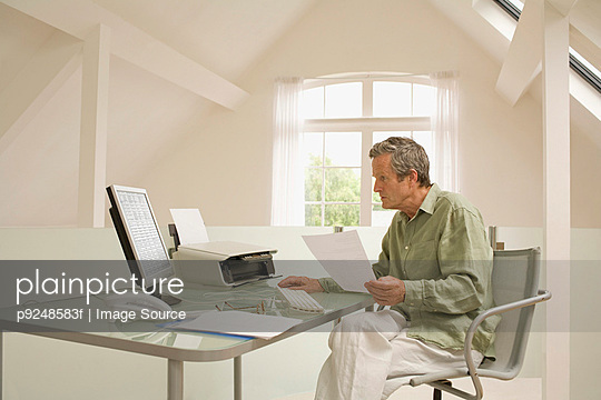 Man using computer - p9248583f by Image Source