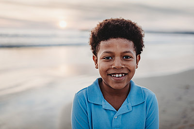 Portrait of young school-aged boy smiling at beach during sunset - p1166m2163265 by Cavan Images