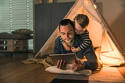 Father and son sharing a tablet at an illuminated tent at home - p300m2104388 by Uwe Umstätter