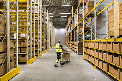 Full length of senior male warehouse worker pushing cart on aisle in industrial building - p426m2018841 by Maskot