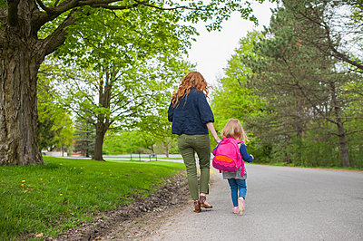 Rear view of mother and daughter holding hands walking down road through woods - p429m821898 by Hugh Whitaker