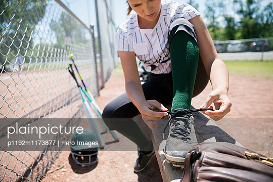Middle school girl softball player tying shoe on bench