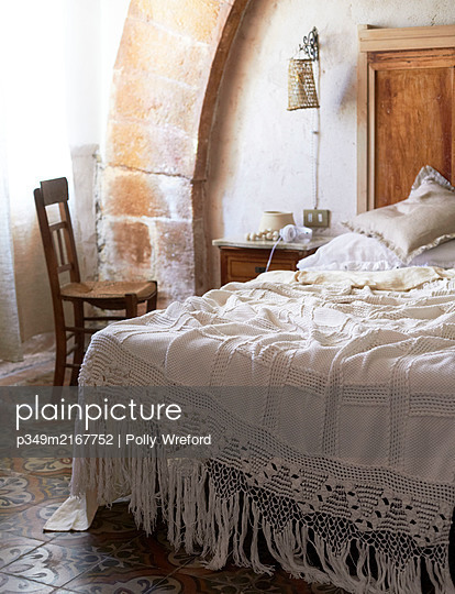 Traditional cover on unmade bed in Sicilian home - p349m2167752 by Polly Wreford