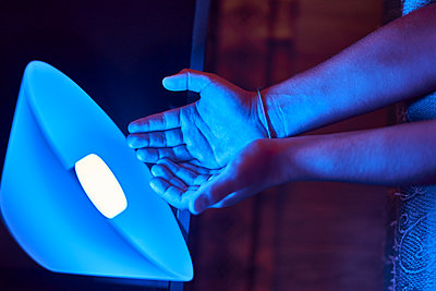 Close Up view of hands illuminated by a blue light bulb led light - p1166m2072003 by Cavan Images