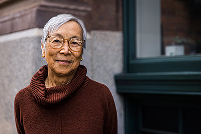 Portrait of smiling senior woman wearing glasses in the city - p1166m2285617 by Cavan Images