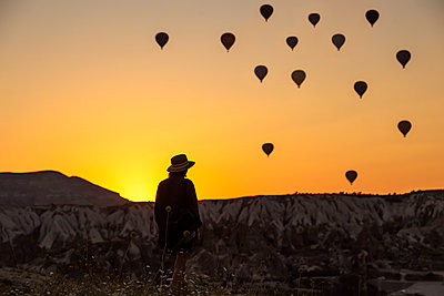 Rear view of silhouette young woman looking at hot air balloons while standing on land in Goreme, Cappadocia, Turkey - p300m2198486 by Konstantin Trubavin