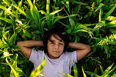 Smiling boy resting while lying on grass in meadow - p300m2221328 by Valentina Barreto