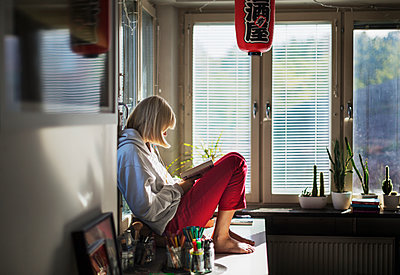 Teenage girl reading book at home - p312m2080325 by Pernille Tofte