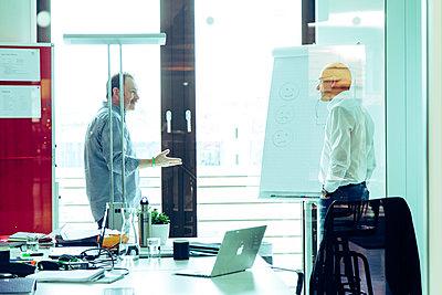 Zwei Männer unterhalten sich im Büro - p317m1488104 von Nina Steul