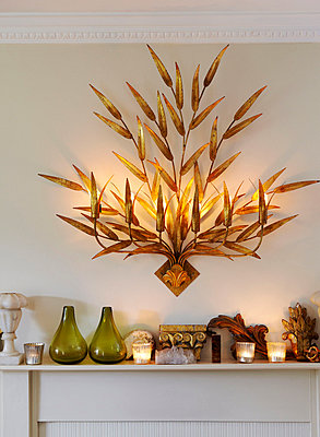Decorative light fitting above mantlepiece with ornaments - p349m790268 by Brent Darby