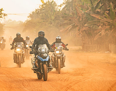 Male friends riding ADV motorcycles on dusty rural road in Cambodia, rear view - p429m2091727 by Henn Photography