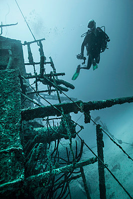 Diver examining underwater shipwreck - p429m743960 by Zac Macaulay